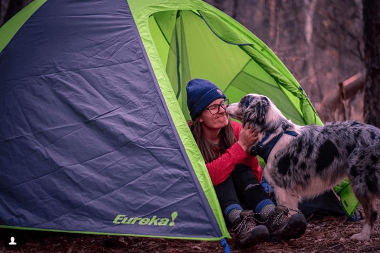 Woman and dog sitting in an Eureka tent