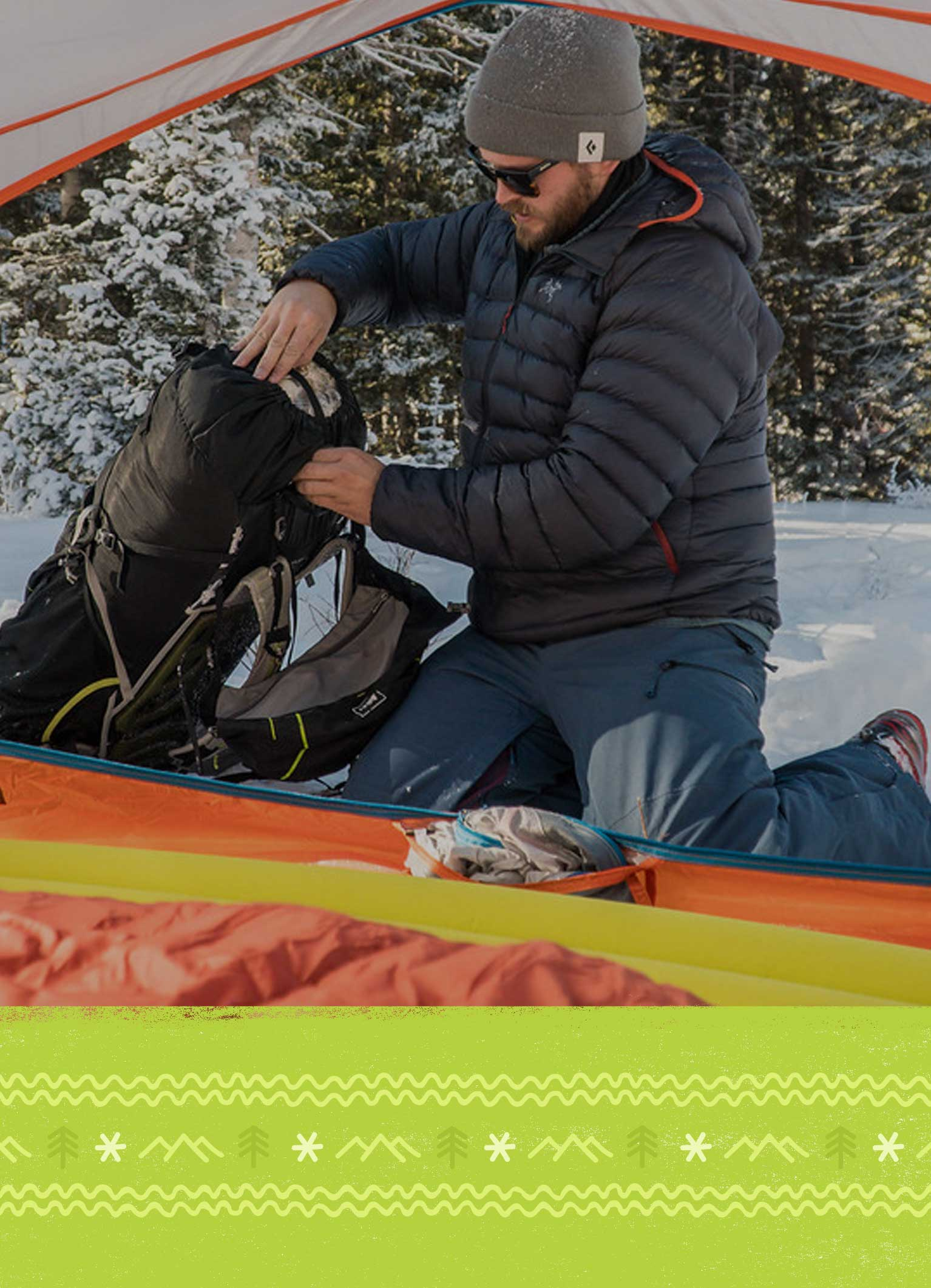 Backpacker unpacking and setting up camp in the snow